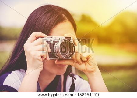 Female photographer with sunglasses holding professional digital camera vintage style. Asian woman taking picture on blurred nature background. Outdoor at the daytime with sunlight. Warm tone.