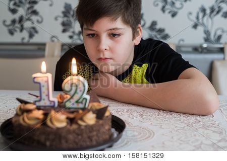 Teen boy looks thoughtfully at a cake with candles on the twelfth day of birth