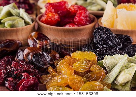 Assortment of dried fruits closeup on brown wooden background. Decorative border of dry exotic fruit in spoons bowl.