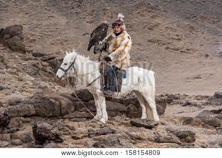 Thailand tourist in Mongolia traditionally riding horse with Kazakh Eagle Hunter in a desert mountain. Ol-geiWestern Mongolia.