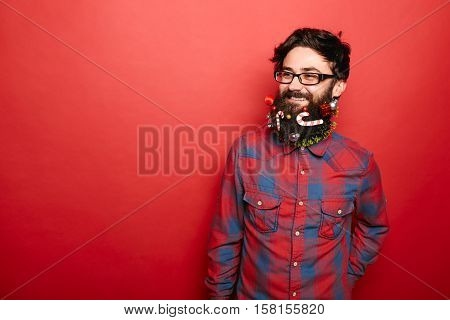 Geeky hipster man with decorated christmas beard looking to the side to copy space on red color background