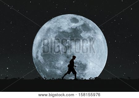 Silhouette a man walking under full moon at night with stars on the sky