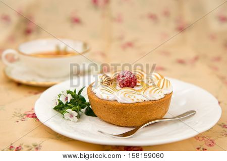 Raspberry and custard tart on a white plate