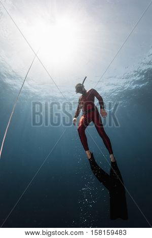 Underwater shot of the ascending free diver. Free immersion discipline