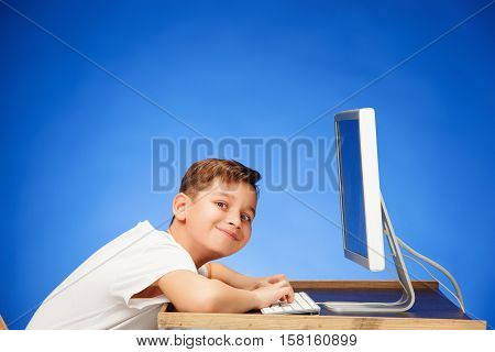 School-age boy sitting in front of the monitor laptop at blue studio backgroubd