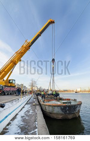 MOSCOW, RUSSIA - NOVEMBER 11, 2016: State Unitary Enterprise Mosvodostok performs recovery vessels on coastal winter parking. Dockers slings to lift the barge from the river.