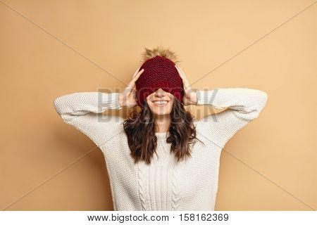 Beautiful happy young Caucasian brunette woman wearing white sweater smiling and covering eyes with her beanie red hat isolated on beige background