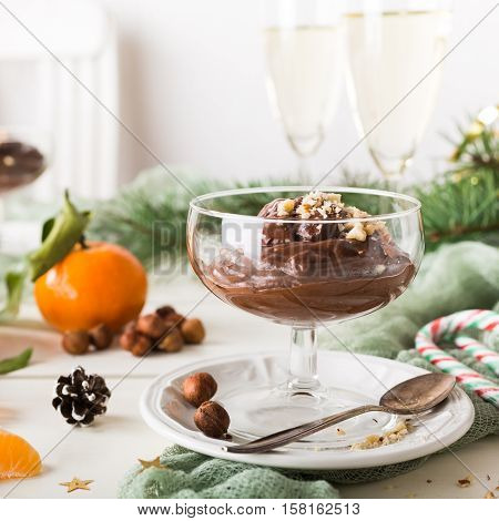 Chocolate pudding mousse with avocado, nuts and christmas decorations. Delicious Christmas themed dinner table.
