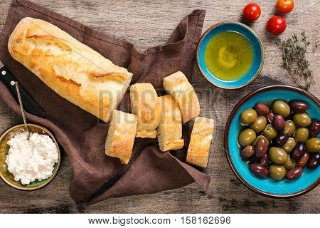 Fresh Italian baguette cut in slices on wooden table with oil olives garlic herbs goat cheese and cherry tomatoes top view. Ingredients for making bruschetta