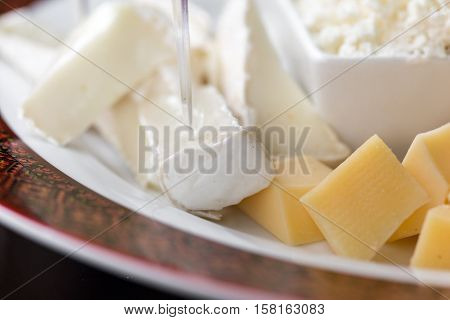 Set of different cheeses brie cheese mozzarella and feta cheese on plate close up
