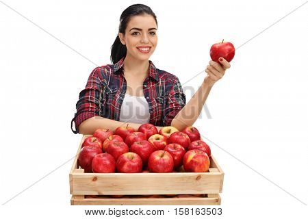 Cheerful female farmer holding an apple behind a crate full of apples isolated on white background