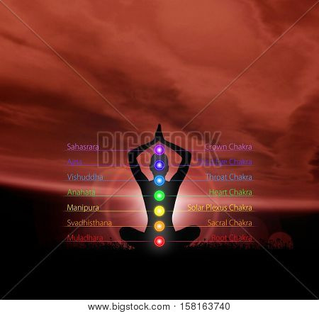 Silhouette of monk meditating in lotus position. Colored chakra lights over body. Yoga, zen, Buddhism, recovery, religion and wellbeing concept.