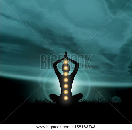 Silhouette trace of human meditating in lotus position. Colored chakra lights over body. Yoga, zen, Buddhism, recovery, religion, healthcare and wellbeing concept.