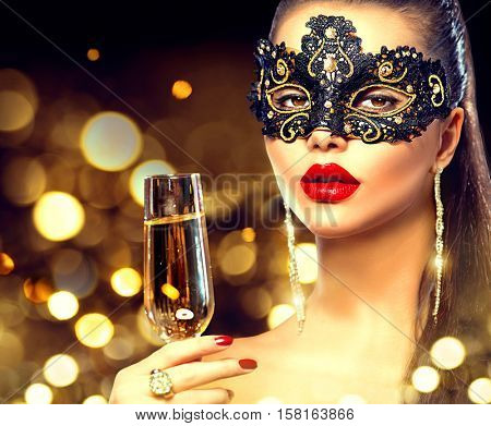 Beauty Glamour Woman celebrating with champagne, wearing carnival mask. party, drinking champagne over holiday glowing background. Christmas and New Year celebration