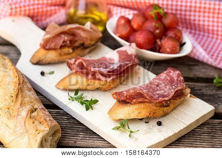 Italian antipasti bruschettas with ham prosciutto coppa salami and cherry tomatoes
