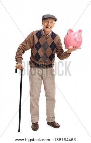 Full length portrait of a cheerful senior with a cane and a piggybank isolated on white background