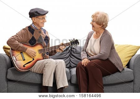 Elderly man sitting on a sofa and playing a guitar to an elderly woman isolated on white background