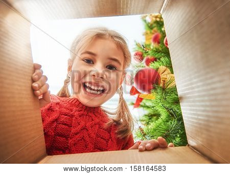 Merry Christmas and Happy Holidays! Cheerful cute child girl opening a Christmas present. Little kid having fun near Christmas tree indoors. View from inside of the box.