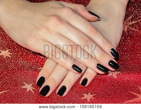 Beautiful women hands with black manicure Black nail polish. Manicured nail with black nail polish.