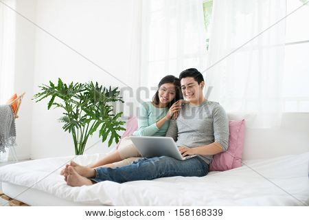 Young asian couple browsing internet at homeusing laptop and smiling