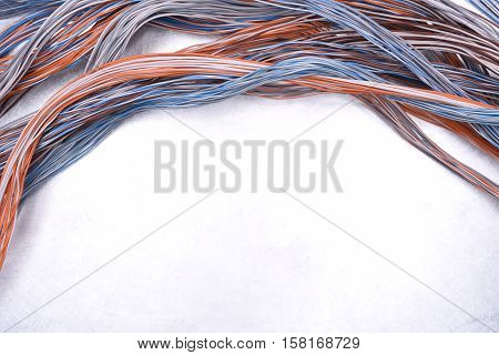 Cables and wires of electrical and telecommunication network on grey metal surface, copy space