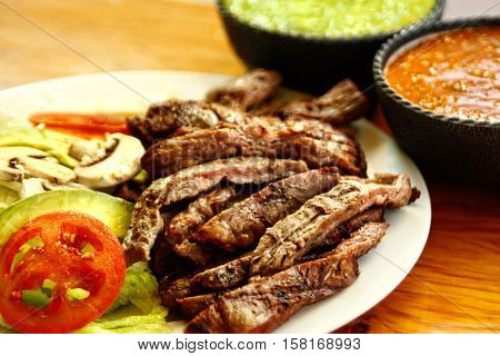 Beef fajitas on a white plate with sauces