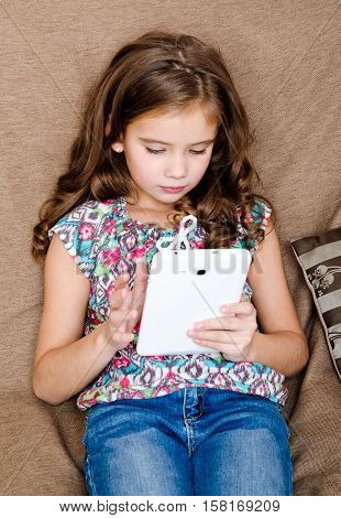 Cute little girl with tablet pc on the sofa at home education and internet concept