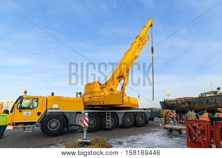 MOSCOW, RUSSIA - NOVEMBER 11, 2016: State Unitary Enterprise Mosvodostok performs recovery vessels on coastal winter parking. Vehicle crane in the operative position, mounted on metal supports.