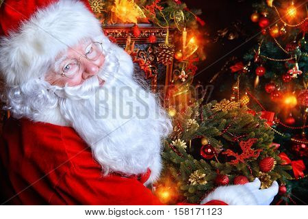 Santa Claus in his house next to the fireplace and Christmas tree holds a Christmas wreath.