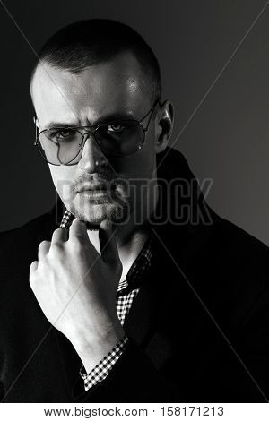 Black-and-white portrait of a  pensive handsome man. Short hair styling. Studio fashion shot.