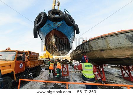 MOSCOW, RUSSIA - NOVEMBER 11, 2016: State Unitary Enterprise Mosvodostok performs recovery vessels on coastal winter parking. Workers attach the ship to berth.