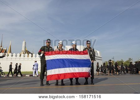 BANGKOK THAILAND - NOV 22 : soldier hold National flag with pride after national ceremony for king near Sanam Luang while the funeral of king Bhumibol Adulyadej in Grand Palace on november 22 2016