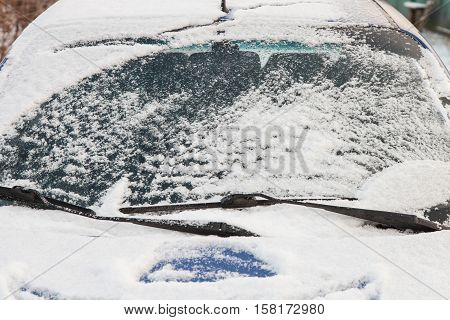 Windshield of the car covered with snow