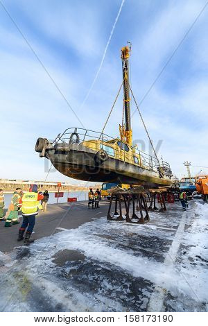 MOSCOW, RUSSIA - NOVEMBER 11, 2016: State Unitary Enterprise Mosvodostok performs recovery vessels on coastal winter parking. Truck crane lowers the vessel to metal supports
