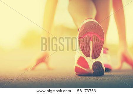 Runner feet running on road closeup on shoe. woman fitness sunrise jog workout welness concept on sunset.