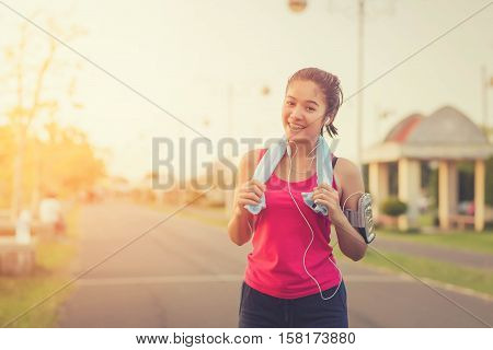 Young woman runner wearing armband and listening to music on earphones. Fit sportswoman taking a break from outdoors training.