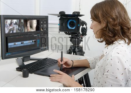 young female designer using graphics tablet for video editing
