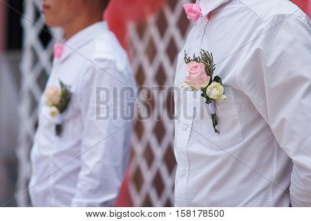 friends of the groom at the wedding ceremony with the buttonhole on the shirt.