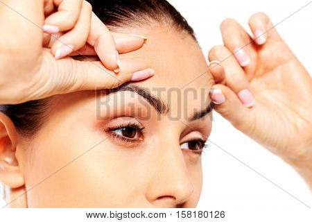Worried young woman checking wrinkles on forehead