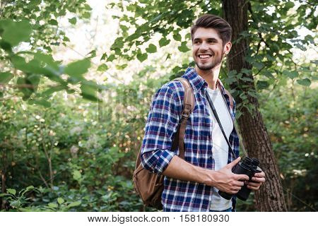 Portrait of smiling male hiker in forest. stands sideways. man in shirt with backpack and binoculars