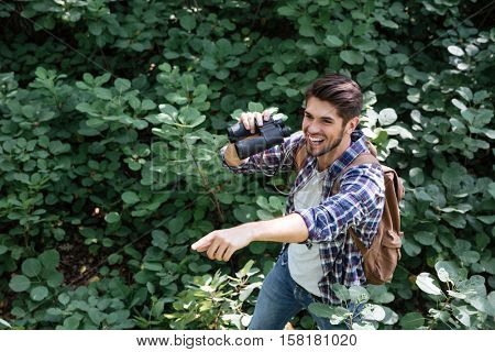 Young man with binoculars in forest show ourselves. from above image