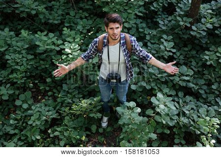 Misunderstood man in forest. from above image. top view. man with binoculars and backpack