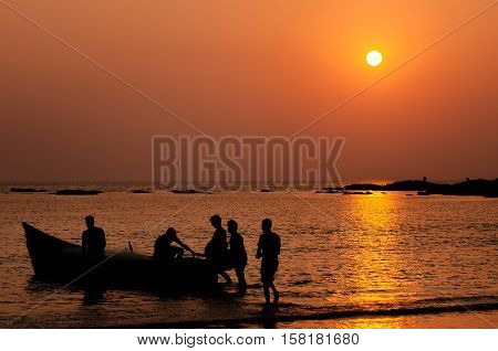Silhouettes of fishermen going to fishing on a boat in the sea at sunset at night and comeback in sunrise Goa India.