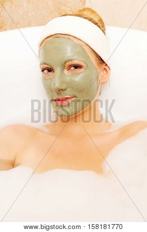 Woman with facial mud mask. Dayspa