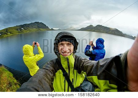 hikers on the Lake coast with mountain reflection at the rainy day, Iceland. Two hikers take pictures of the lake, and one take selfie
