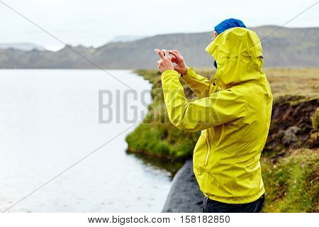 hikers on the Lake coast with mountain reflection at the rainy day, Iceland. Two hikers take pictures of the lake