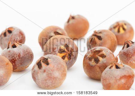 Raw common medlar fruits on white background. Healthy food background.