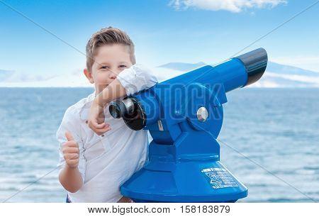 Boy near the scoping public binocular telescope (binoscope) near the sea in Spain. Travel concept.