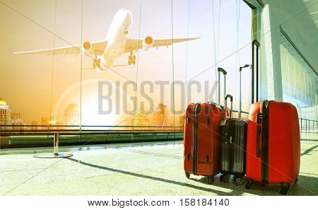 stack of traveling luggage in airport terminal building and passenger plane flying over urban scene