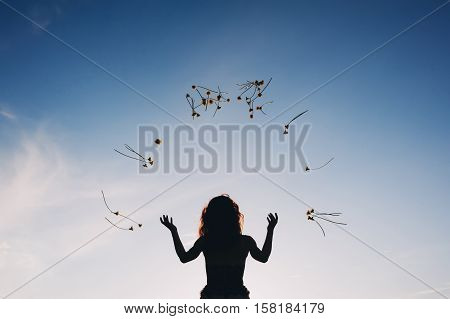 A young woman throws yellow flowers in the air against the blue sky. dandelions